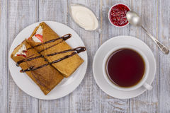 Pancakes with cottage cheese and cup green tea on the wooden table Stock Images