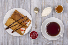 Pancakes with cottage cheese and cup green tea on the wooden table. Close up Stock Photos