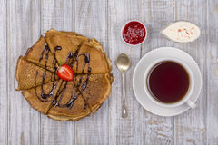 Pancakes with cottage cheese and cup green tea on the wooden table. Close up Royalty Free Stock Photos