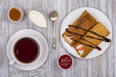 Pancakes with cottage cheese and cup green tea on the wooden table. Pancakes with cottage cheese and strawberries poured with chocolate and cup tea on the white Royalty Free Stock Images