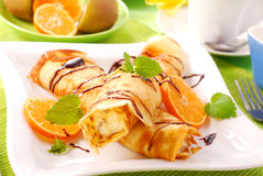 Pancakes with with cottage cheese and orange. Rolled pancakes with cottage cheese and orange poured chocolate Royalty Free Stock Photography