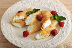 Pancakes with cottage cheese and raspberries on a plate. On wooden background Stock Photos