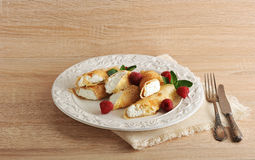 Pancakes with cottage cheese and raspberries on a plate. On wooden background Stock Photo