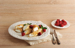 Pancakes with cottage cheese and raspberries on a plate. On wooden background Royalty Free Stock Image