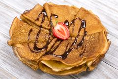 Pancakes with cottage cheese, strawberry, chocolate on the wooden table. Close up Stock Photos