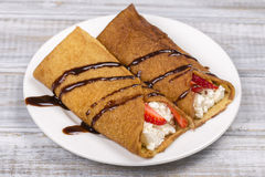 Pancakes with cottage cheese, strawberry, chocolate and on the wooden table Stock Photo