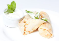 Pancakes with cottage cheese on a white plate. Sour cream next to them Stock Photos