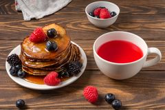Pancakes covered by honey with blueberries and strawberries and cup of red juice on wooden background. View of a pancakes covered by honey with blueberries and royalty free stock image