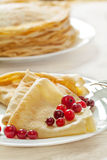 Pancakes with cranberries served on white table Stock Image
