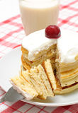 Pancakes with cream and cherries. A stack of pancakes with whipped cream and cherries on a checkered tablecloth Stock Image
