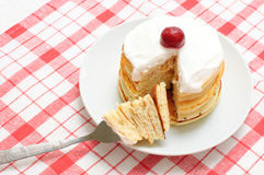 Pancakes with cream and cherries. A stack of pancakes with whipped cream and cherries on a checkered tablecloth Stock Images
