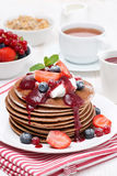 Pancakes with cream, fruit sauce and berries for breakfast Royalty Free Stock Photos