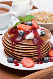 Pancakes with cream, fruit sauce and fresh berry on wooden tray Stock Images
