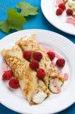 Pancakes with cream and raspberries stock photo
