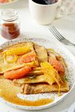 Pancakes crepe Suzette for breakfast with orange caramel sauce, orange slices, lime and orange zest and a cup of coffee. Dessert French cuisine. Sunday royalty free stock images