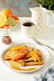 Pancakes crepe Suzette for breakfast with orange caramel sauce, orange slices, lime and orange zest and a cup of coffee. Dessert French cuisine. Sunday royalty free stock image