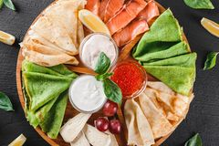 Pancakes or crepes with filet salmon, red fish caviar, sour cream sauce. Cheese sauce on wooden board on dark background. Appetizer food concept. Top view stock photo