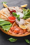 Pancakes or crepes with filet salmon, red fish caviar, sour cream sauce. Cheese sauce on wooden board on dark background. Appetizer food concept. Top view stock photos