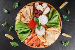 Pancakes or crepes with filet salmon, red fish caviar, sour cream sauce, cheese sauce on wooden board on dark background. Appetizer food concept. Top view royalty free stock photo