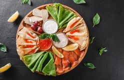 Pancakes or crepes with filet salmon, red fish caviar, sour cream sauce, cheese sauce on wooden board on dark background. Appetizer food concept. Top view stock photo