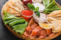 Pancakes or crepes with filet salmon, red fish caviar, sour cream sauce, cheese sauce on wooden board on dark background. Appetizer food concept. Top view stock photos