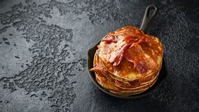 Pancakes with crispy bacon and maple syrup in cast iron skillet, frying pan. Morning Breakfast royalty free stock photo
