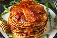 Pancakes with crispy bacon and maple syrup in a plate. Morning Breakfast royalty free stock images