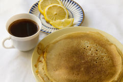 Pancakes with a Cup of coffee and lemons on a plate. Breakfast. Pancakes with a Cup of coffee and lemons on a plate. Delicious Breakfast royalty free stock image