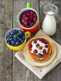 Pancakes with curd and fresh berries. Pancake with curd and fresh berries and a bottle of milk Royalty Free Stock Photo