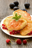Pancakes decorated with red currant berries. On wooden table Stock Photos