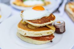 Pancakes with deep fried bacon, fried potato with peel and fried egg on the top served with maple syrup at restaurant in Dubai.  royalty free stock images