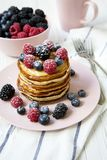 Pancakes with different berries in pink plate on table. Side view Stock Photography
