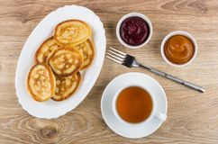 Pancakes in dish, fork, bowls with jam and tea Royalty Free Stock Photos