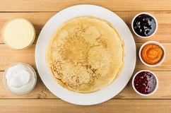 Pancakes in dish and jam, condensed milk, sour cream Royalty Free Stock Photo