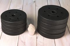 Pancakes for dumbbells on the wooden floor and protein. Sport equipment stock photography