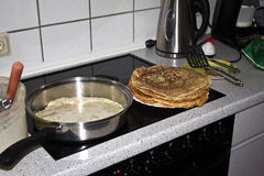 Pancakes. On an electric stove is a frying pan and a plate of pancakes royalty free stock images