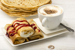 Pancakes filled with cottage cheese and cup of coffee on the wooden background. Royalty Free Stock Photos