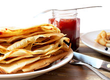 Pancakes filled with homemade strawberry jam. Plate with pancakes filled with strawberry jam, a jar with homemade jam Royalty Free Stock Photos