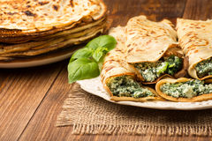 Pancakes filled  with spinach and cheese  on the wooden surface. Royalty Free Stock Photos