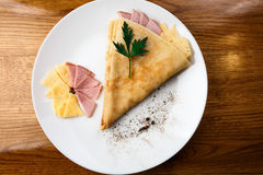 Pancakes with fillings. cheese and ham. White plate Royalty Free Stock Image