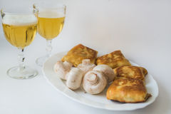 Pancakes with fillings and mushrooms on plate. Fried pancakes with fillings, mushrooms and glass of beer in the white plate on a white background Royalty Free Stock Photo
