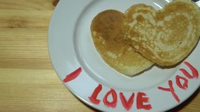 A plate with pancakes in the form of a heart and a mug with coffee on a table. Pancakes in the form of heart lie on a plate on the edge of which words are stock video footage