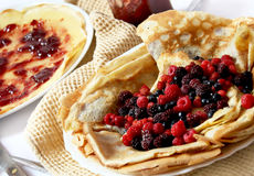 Pancakes with fresh berries. Plate with fresh berries and pancakes filled with homemade jam placed over a napkin stock photo