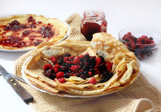 Pancakes with fresh berries and homemade jam. Plate with fresh berries and pancakes filled with homemade jam placed over a napkin stock photos