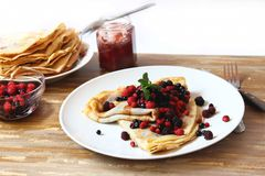 Pancakes with fresh berries , jam and mint. Plate with fresh berries and pancakes filled with homemade jam placed over a napkin Stock Photography