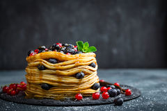 Pancakes with fresh berries and maple syrup on dark background. Closeup royalty free stock images
