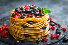 Pancakes with fresh berries and maple syrup on dark background. Closeup stock image