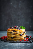 Pancakes with fresh berries and maple syrup on dark background. Closeup stock images