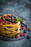 Pancakes with fresh berries and maple syrup on dark background. Closeup stock photography