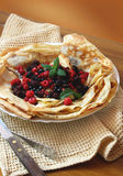 Pancakes with fresh berries and mint. Plate with fresh berries and pancakes filled with homemade jam placed over a napkin stock images